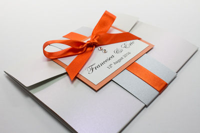 Bespoke pocketfold wedding invitation in moonstone with flame orange ribbon